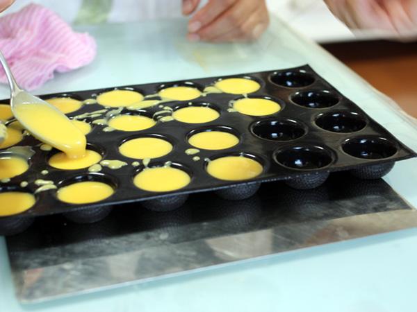 先ほどのポンポネット型に柑橘系のクリームを流していきます。これだけでも美味しそう。